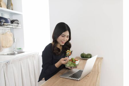 Young woman with salad working on laptop in the kitchen