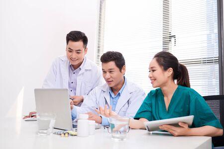 concept d'hôpital, de profession, de personnes et de médecine - groupe de médecins heureux avec des ordinateurs tablettes se réunissant au cabinet médical