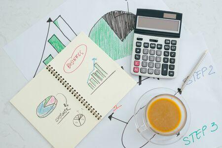 Geschlossen und weicher Fokus auf Stift, der auf Papierkram mit Taschenrechner für zusammenfassendes Einkommen oder Gewinn am Schreibtisch legt. Standard-Bild