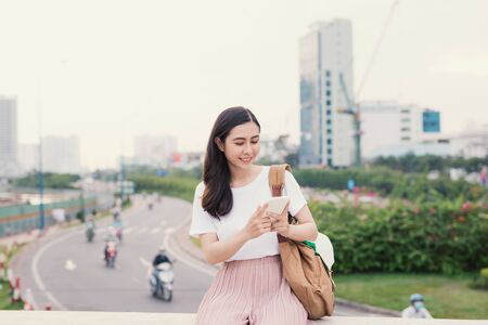 Young woman using a smart phone sitting with bag in city background