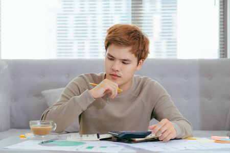 young attractive Young Asian man at home sitting on sofa with calculator accounting costs, charges, taxes and mortgage for paying bills looking worried and stressed Banco de Imagens