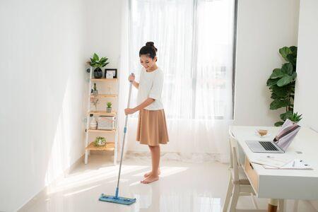 Mujer asiática joven que hace la limpieza en la oficina en casa.