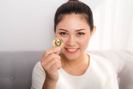 Asian woman gets big money! Attractive woman with holds bitcoin in hands and looks into the camera. Stock fotó