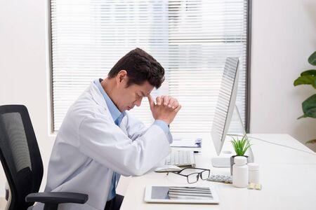 Docteur surmené assis dans son bureau