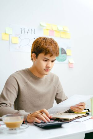 Stressed Asian Business man due to the of amount of work he has to do.
