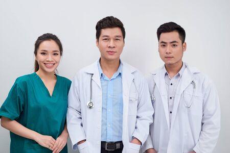 Grupa azjatyckich pracowników medycznych / lekarzy i pielęgniarki uśmiecha się do kamery
