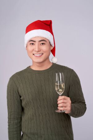 Celebration and New Year. Asian man holds glass of champagne