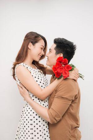 Ritratto di una bella coppia allegra e carina con sorrisi raggianti che si abbracciano e si guardano l'un l'altro, Archivio Fotografico