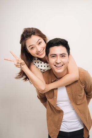 Mann trägt seinen Liebhaber auf dem Rücken, Frau zeigt Friedenssymbol auf weißem Hintergrund Standard-Bild
