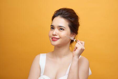 Joven y bella mujer asiática mantenga una pipeta de suero para la piel sobre fondo amarillo