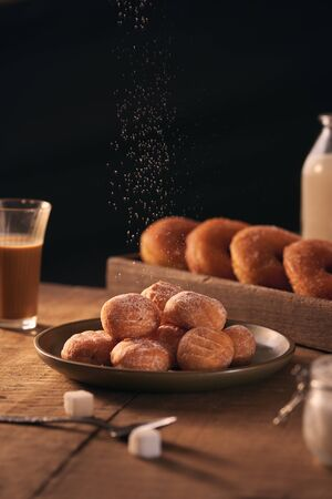 Small balls of freshly baked homemade cottage cheese doughnuts in a plate on a gray background.