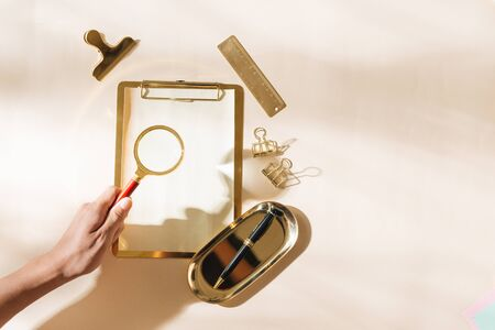 Woman holding magnifying glass over gold stationery on light background