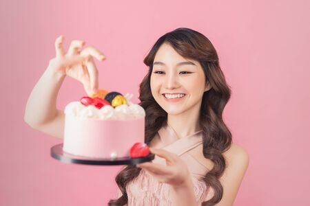 Generous woman holding birthday cake front pink background