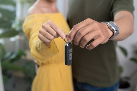Young couple holding up new car key