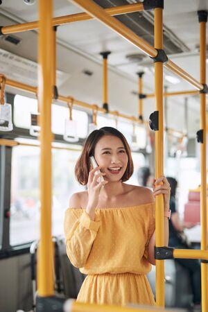 Asian girl using phone on public bus