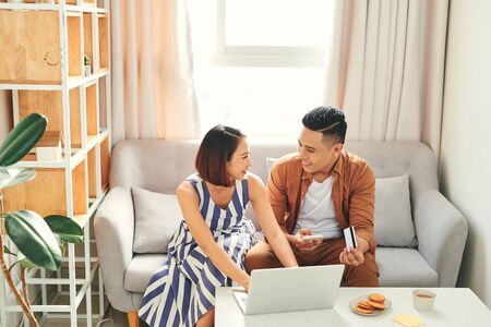 Young Asian couple paying bills by laptop and smartphone with credit card at home Stockfoto