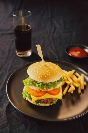 Unhealthy concept. unhealthy food: Burger, sauce, potatoes, cola.