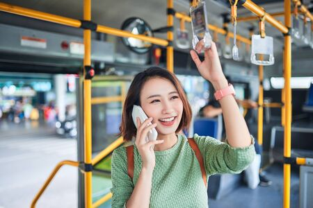 Beautiful young woman standing in city bus and talking on mobile phone. Banco de Imagens