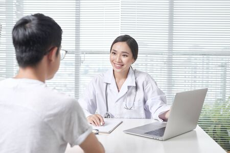 Beautiful female doctor in white medical coat is consulting her patient