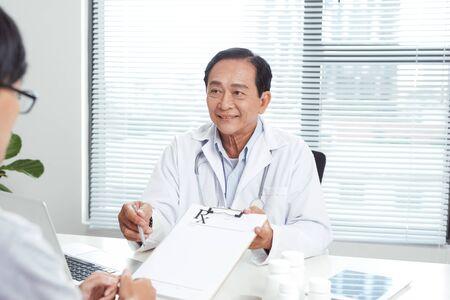 Médico senior consulta paciente joven
