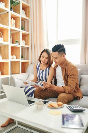 Smiling young couple sit on couch using laptop taking care of utility bills and house, read paperwork