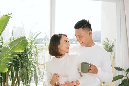 Happy Asian Lovers hugging  holding a cup of water in living room