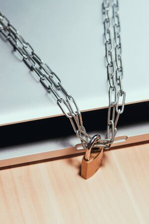 Heavy chain with a padlock around a laptop on table. Imagens