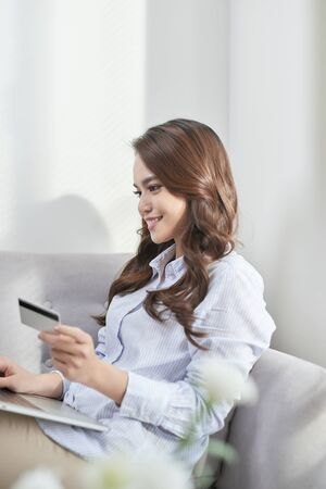 A beautiful using laptop and her bank card while shopping from home without living sofa