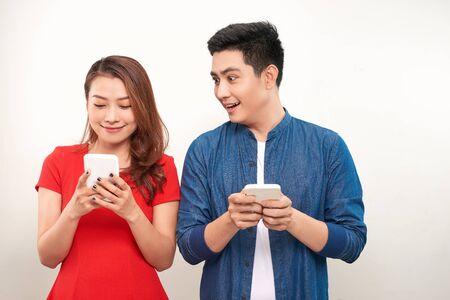 Pareja asiática usando gadgets: chica guapa escribiendo un mensaje en el teléfono celular mientras su novio está de pie junto a ella, mirando la pantalla de su teléfono inteligente