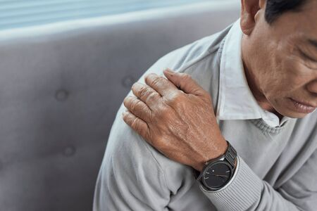 Old senior man with shoulder pain. Grandpa with shoulder inhury at home