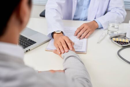 Asian doctor consults young patient