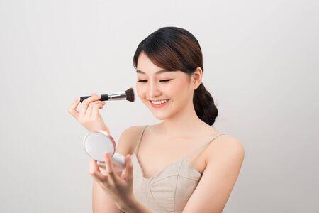 Retrato de una joven y bella mujer aplicando base con pincel negro.