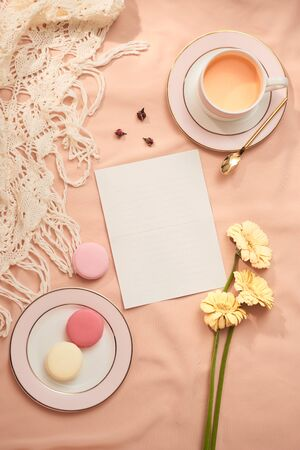 Envelope, flowers, and macarons with cup of tea on light background