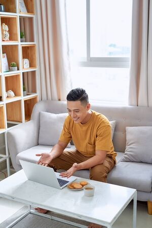 Young man is browsing at his laptop and calling with customer on the sofa at home, Business success