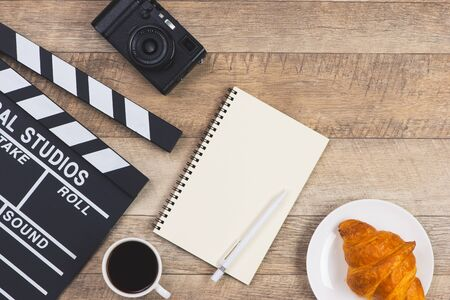 Movie clapper with paper, pen, cake and cup of coffee on wooden planks background