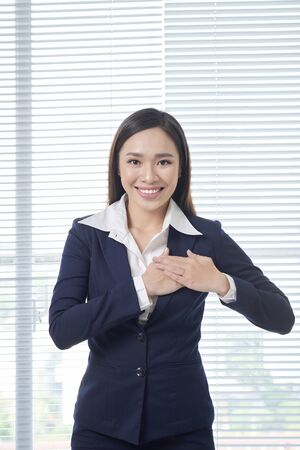 smiling positive young woman keeps hands on chest, expresses sympathy Foto de archivo - 133120450