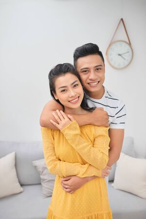 Romantisches junges Paar umarmt im Wohnzimmer