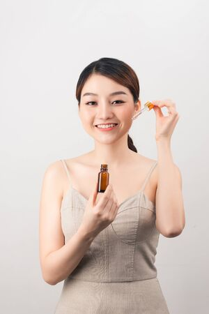 Young amazing woman posing isolated over white background holding oil drop serum. 版權商用圖片