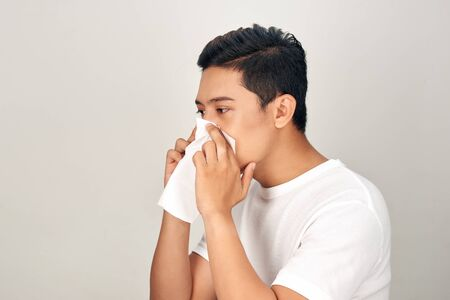 Closeup of sick Asian man blowing nose into tissue, suffering from common cold. Medical and healthcare concept on white background