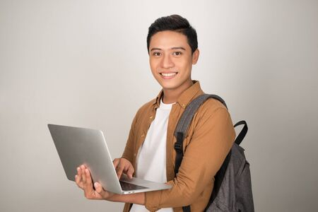 A handsome young student using laptop and carrying backpack isolated on white background