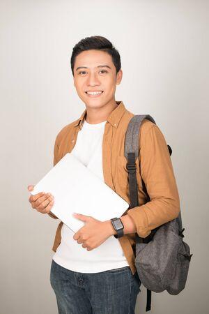 Retrato de muchacho universitario de adolescentes asiáticos sosteniendo libros y documentos contra el fondo blanco.