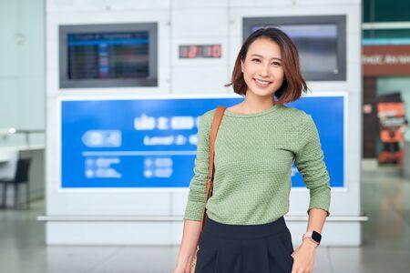 Reizen. Jonge vrouw gaat op luchthaven bij raam met koffer wachtend op vliegtuig