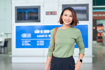 Viaje. Mujer joven va al aeropuerto en la ventana con maleta esperando avión