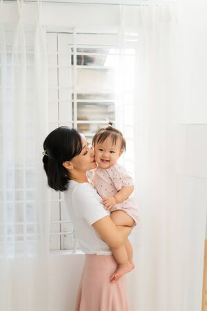 Portrait of happy vietnamese mother hugging with her cute little daughter at home 스톡 콘텐츠