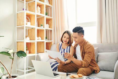 Porträt von schönen jungen asiatischen Paaren, die zu Hause Laptop auf dem Sofa verwenden.