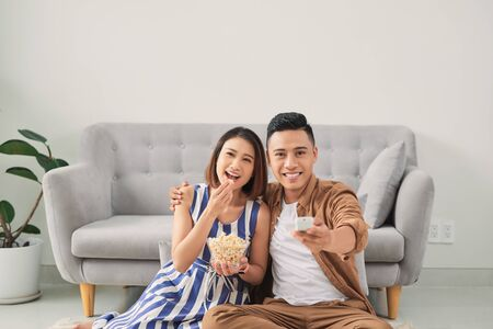 Happy young couple relaxing and watching TV at home.