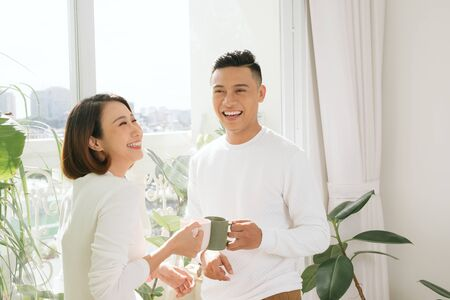 Young asian couple drinking coffee in living room at home
