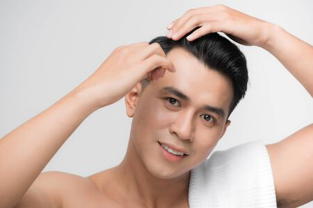 beauty, grooming and people concept - smiling young man brushing hair with comb over white background