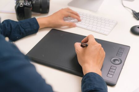 workplace of photographer. Creative designer hands working graphic tablet, photographic equipment on table Stock Photo