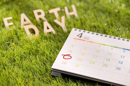 Letter happy earth day concept with calendar on green grass